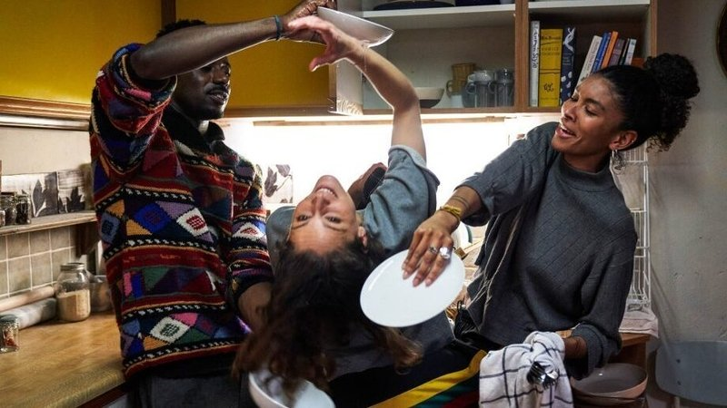 Kieran, Ray and Gemma do the dance of getting dishes in the cramped kitchen of their shared apartment.