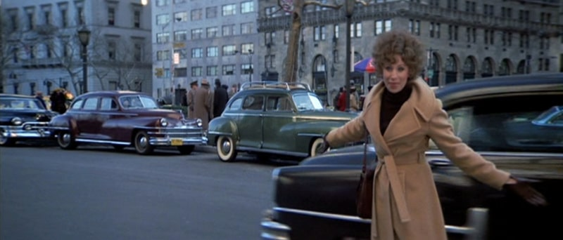 Barbra Streisand, wearing a fawn-coloured coat, stands on the street in New York with her arms spread wide. The image is from the film The Way We Were.