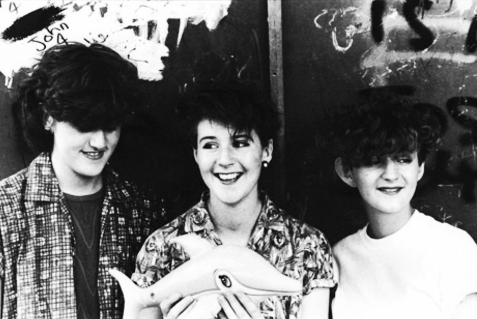 Image shows band The Marine Girls, three young women including Tracey Thorn on the left. They are standing in front of a graffiti'd wall.