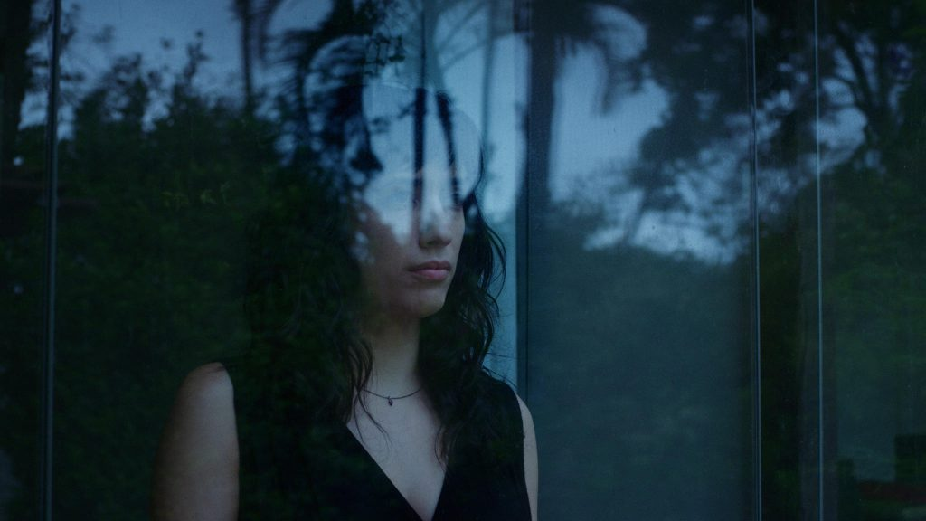 The image shows a woman with dark, below shoulder-length hair, wearing a sleeveless black V-neck top and a choker with a small pendant. She is looking out of the window at trees in leaf, and they are visible reflected in the window.