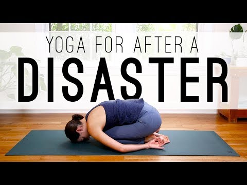 """This image shows a person in a dark blue vest and lighter blue trousers kneeling on a mid-blue yoga mat, with their head pressed to their knees and hands linked behind them, in child's pose. The title on the image reads """"Yoga for After a Disaster"""""""