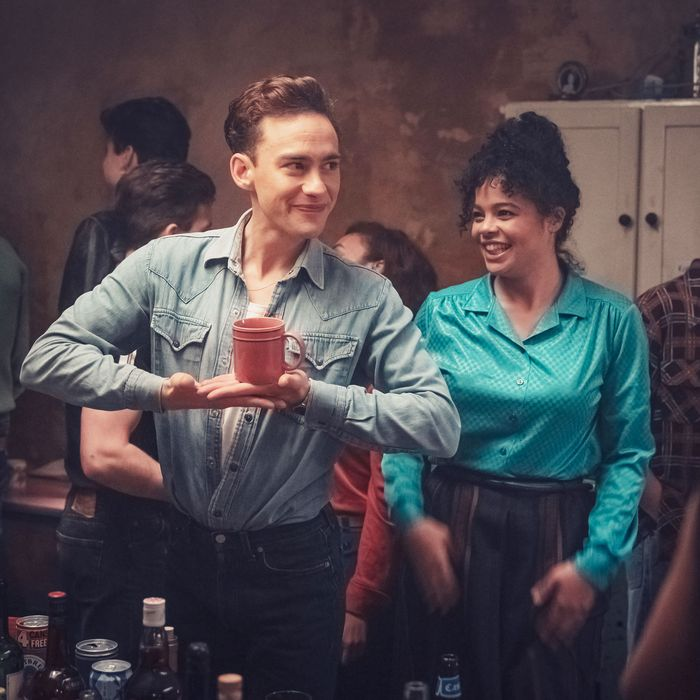 The image is a still from TV show It's a Sin. It shows two people at a party in a flat, with a few people dancing in the background behind them. On the left is Ritchie, a young white man wearing a denim shirt and jeans. He is holding cup before him balanced on his palms in a stylised gesture. On the right is Jill, a young black woman wearing a turquoise shirt and with her hair in a high ponytail. She is smiling and dancing.