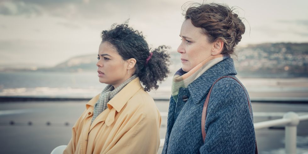 The image is a still from TV show It's a Sin. It shows two characters standing by a white railing, overlooking the sea, with a low rise of land behind them. They are at the harbour on the Isle of Wight. The character on the left is Jill, a young black woman wearing a yellow raincoat over a grey scarf, with her hair tied back in a ponytail with a pink band. The character on the right is Valerie, an older white woman wearing a blue wool coat over a pastel scarf, with her hair pinned up. Both of them look bleak and sad.