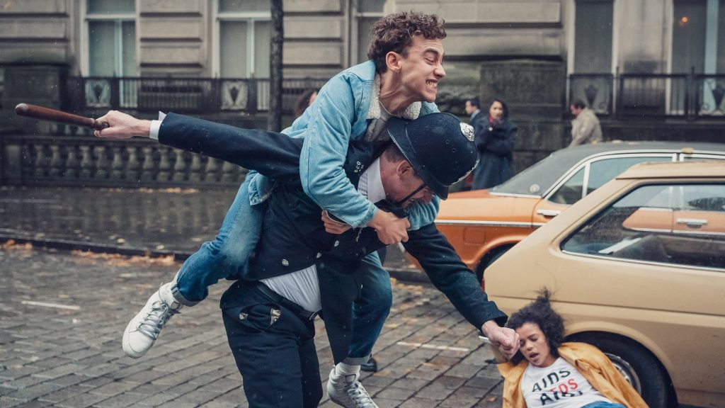 The image is a still from TV show It's a Sin. It shows Ritchie, a young white man in denim jacket and jeans, jumping on the back of a policeman in uniform and helmet. The policeman is swinging his truncheon, which is aimed at Ritchie's friend Jill, a young black woman in a white T-shirt that reads AIDS NEEDS AID. Jill is lying on a cobblestoned road, against the wheel of a taupe car. She has been taking part in a die-in protest in the middle of a London street.