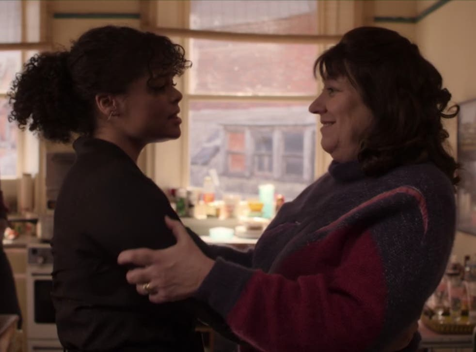 A still from the TV show It's a Sin: two characters embrace before an open window. On the left is Jill, who is wearing a dark brown sweater. On the right is Christine, Jill's mother, wearing a pink cardigan. Jill looks worried and Christine is smiling and embracing her.