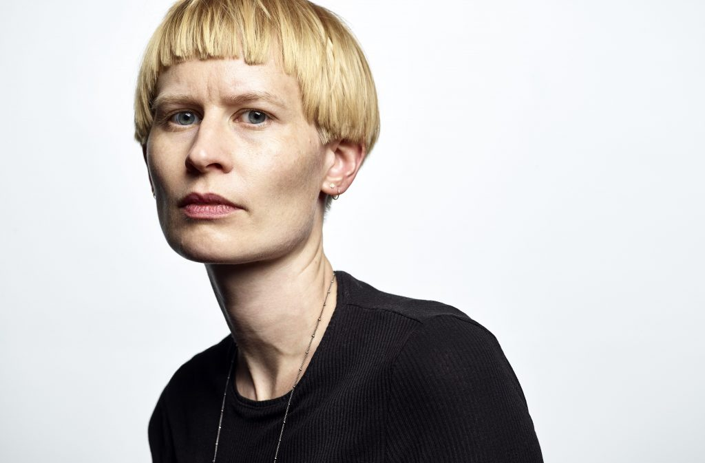 The image is a portrait of the musician Jenny Hval. A very pale-skinned white woman looks directly at the camera. She has slightly gold-toned blonde hair cut in a pudding bowl bob, with a straight fringe. She has slightly recessed blue eyes, a long thin nose and white lips. She is not smiling. She wears a black top with a round neck, and a fine gold chain.
