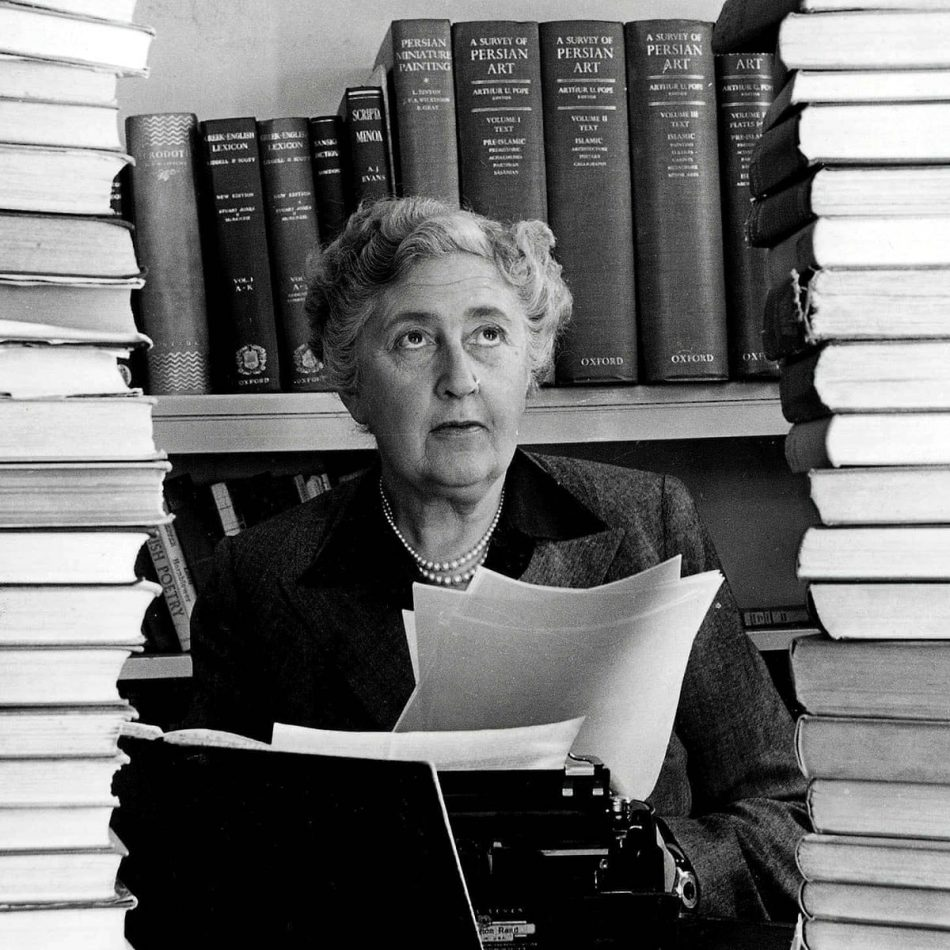 Image is a black and white photograph showing the writer Agatha Christie, an older white woman with white hair. She is wearing a double string of pearls and a dark suit jacket with a darker collar. She is seated behind a typewriter, holding a sheaf of pages, and looking upwards. To either side of her there are stacks of books that fill the frame. There are two shelves of large reference volumes behind her.