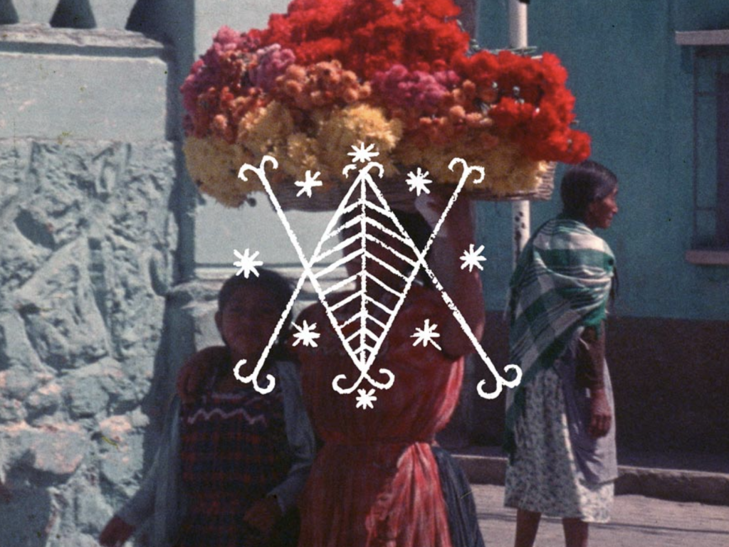 """The image is from Vever (for Barbara), Deborah Stratman (2019). in the foreground, an Indigenous Guatemalan woman in a pink dress carries a large basket of red, pink and orange flowers on her head. She balances the basket with her left hand, and drapes her right arm over the shoulder of a child in a blue shirt and navy blue T shirt with white and red squiggles across the front. Behind them to the left is a grey stone wall; behind them to the right is an older Indigenous woman in a green checked shawl and floral dress, looking right. Behind her, across the street, there is a bright blue wall. Superimposed on the image is a design in white paint: a V and an inverted V forming a diamond at their intersection that is then fletched like a leaf. In the gaps between the crossed lines of the Vs and at their peaks are asterisk-like stars. The design is part of Haitian voudoun practice, and is called a """"vever."""""""