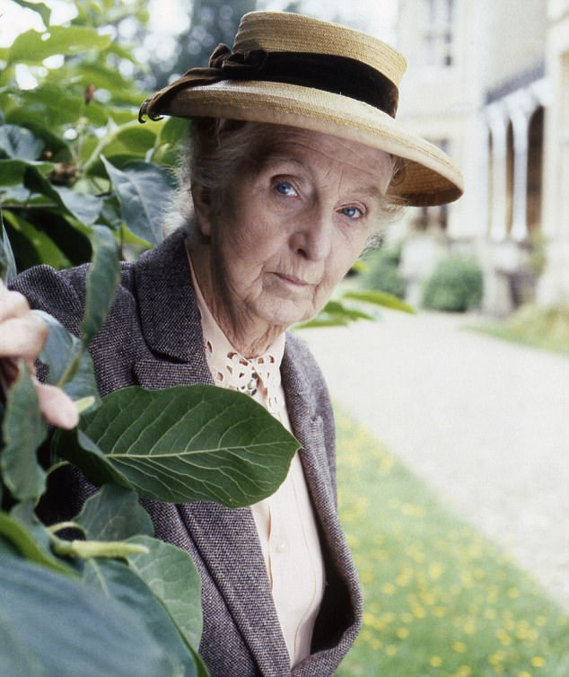 The image shows actress Joan Hickson as Agatha Christie's detective Miss Marple: She is an older white woman with white hair, wearing a straw boater with a black ribbon around it, a grey jacket with a pale gold pinkish blouse with spots on the collar. She is standing behind a tree with large green leaves, peering through them. Behind her, a driveway leads past a flower-scattered lawn to the grand entrance to a country house.