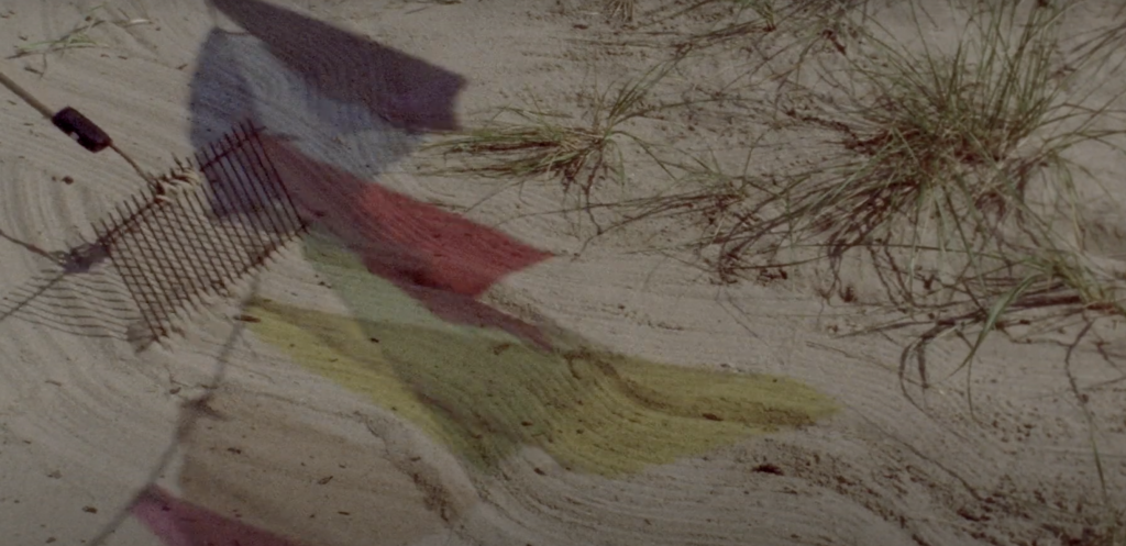An image from A Month of Single Frames, Lynne Sachs (2019). The image shows brightly-coloured shapes cast on a sand dune. On the right of the image, there are a few sparse grasses; on the left the shapes cast by a flag made of blue, white, red and yellow plastic strips with light shining through them. There is also the shadow of a TV aerial, and part of an electrical cable.