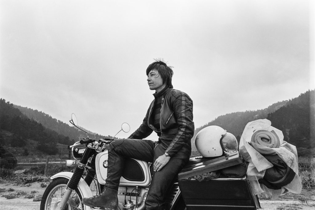 The image is a black and white photograph taken in 1975 that shows the filmmaker Barbara Hammer sitting side saddle on a still motorcycle. She is wearing dark coloured bike leathers and boots, and her short, dark hair is windswept. A bedroll and backpack, each wrapped separately in waterproof plastic, are strapped to the back of the bike, and a bike helmet sits on the half-open pillion, out of which clothing spills. The filmmaker is posed in the foreground against a valley between two hills, so that the curve of her lifted leg balanced on the front of the bike follows the descending curve of the left hill, and the rise of the helmet and luggage follow the shape of the right hill, with the filmmaker's body standing out in the foreground parallel to the lowest point of the valley in the background. The slopes are wooded with firs, and the foreground area around the bike is sandy.