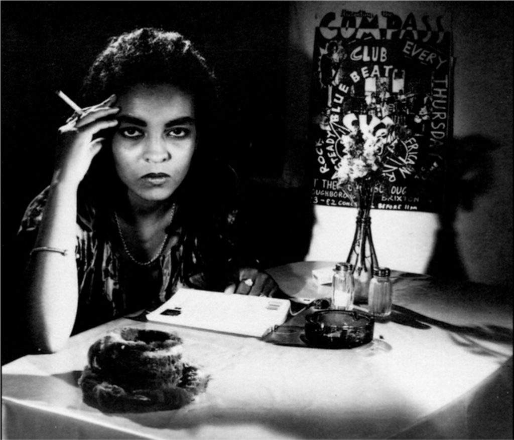 The image is a black and white photograph. It shows a dark-skinned woman with dark curly hair sitting behind a table, holding an unlit cigarette in her right hand, which is also supporting her head. She looks straight at the viewer. In front of her on the table there is a book and a glass ashtray, salt and pepper shakers, and a vase of flowers. Behind the vase, on the wall, there is a collaged poster for the Compass Club. By her right elbow, in the foreground of the image, there is a fur-covered cup and saucer.