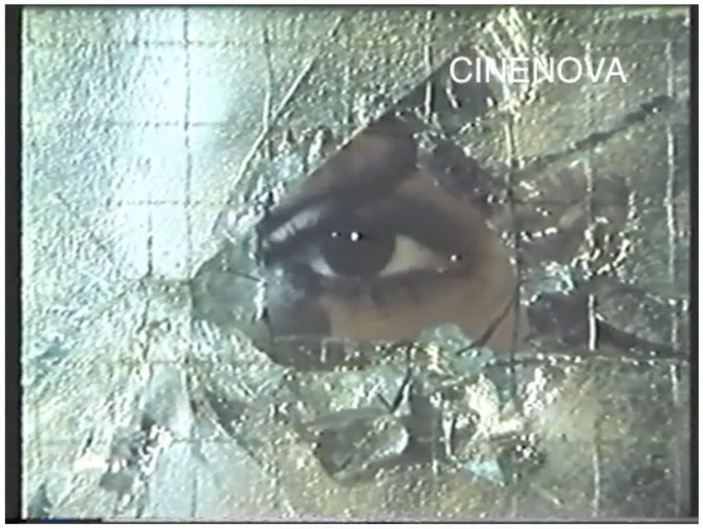 The image is a screen capture from a colour film. It is watermarked CINENOVA in the upper-right hand corner. A dark brown eye peers at the viewer through a fractured pane of silvery frosted glass.