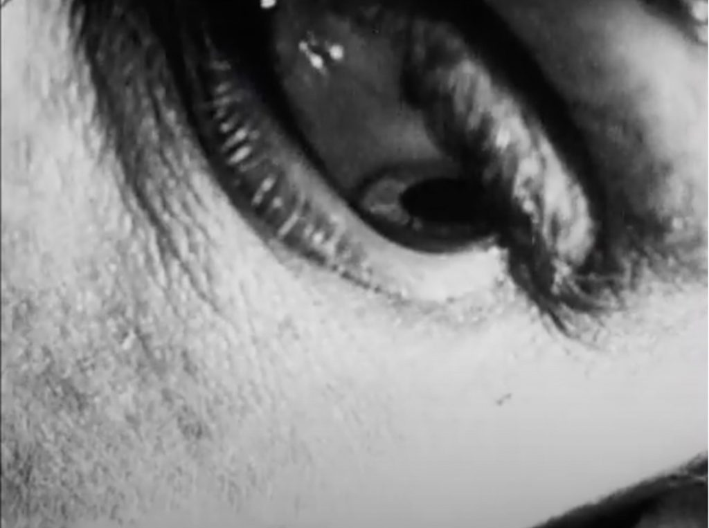 The image is a still from a black and white film. It is an extreme close up of an eye, underage and part of a cheek, seen as if the person were lying on a pillow. The eye is looking down.