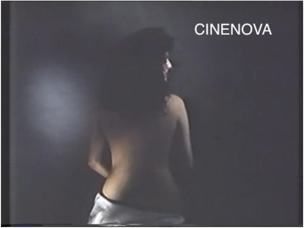 The image is a screen capture from a colour film, watermarked CINENOVA in the upper right hand corner. It shows a pale-skinned woman with long, dark curly hair, sitting with her back to the camera. She has a sheet draped around her hips, and her back and arms are bare. She is shown in profile, looking to the right. The background is a smoky grey.