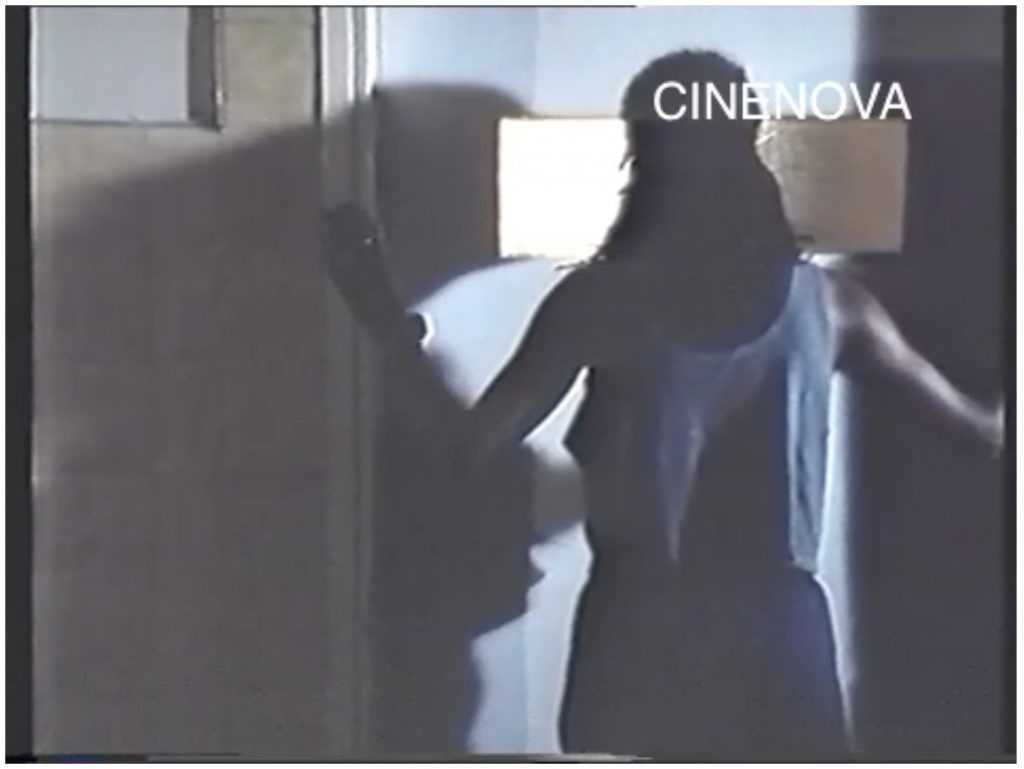 The image is a screengrab from a colour film, watermarked CINENOVA in the upper right hand corner. It shows a dark-skinned woman with mid-back length dark hair in a blue smock and shorts with her back to the camera. She has her arms out, and one hand resting on a door frame. There is a window or light box in front of her.