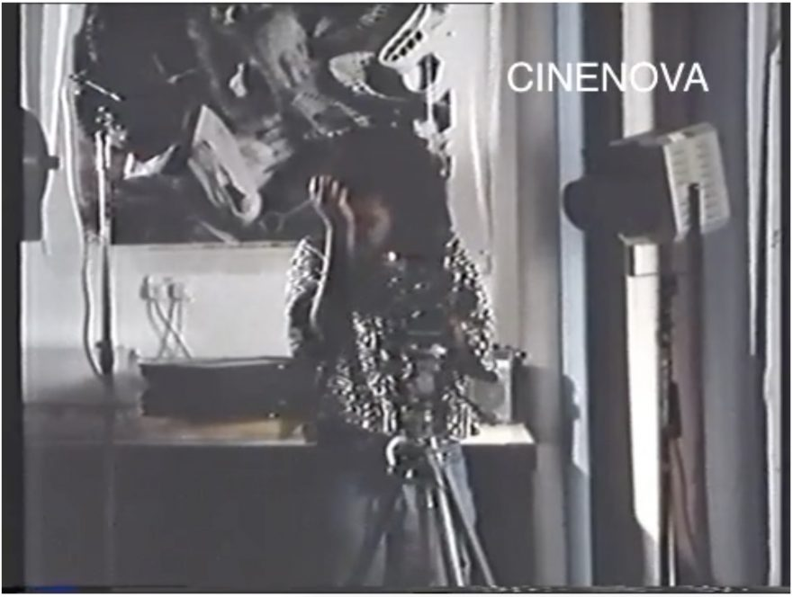 The image is a still from a colour film, watermarked CINENOVA in the upper right hand corner. It shows a dark-skinned woman wearing a silver blouse and grey slacks. She is standing behind a camera on a tripod. There are camera lights in front of her, and an abstract black and white image on the wall behind her.