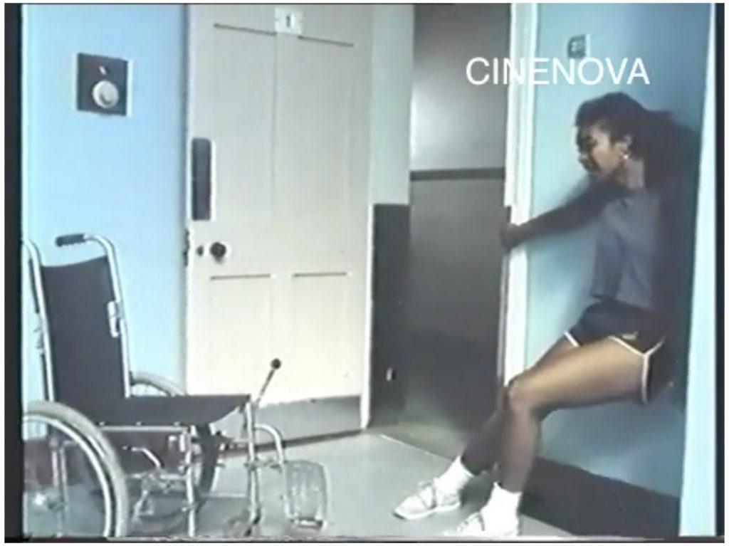 The image is a screen capture from a colour film, watermarked CINENOVA in the upper right hand corner. It shows a dark-skinned woman in black shorts, a grey T-shirt and white trainers balancing with her back against a wall and her knees bent. There is a black wheelchair with self-drive gears facing her.