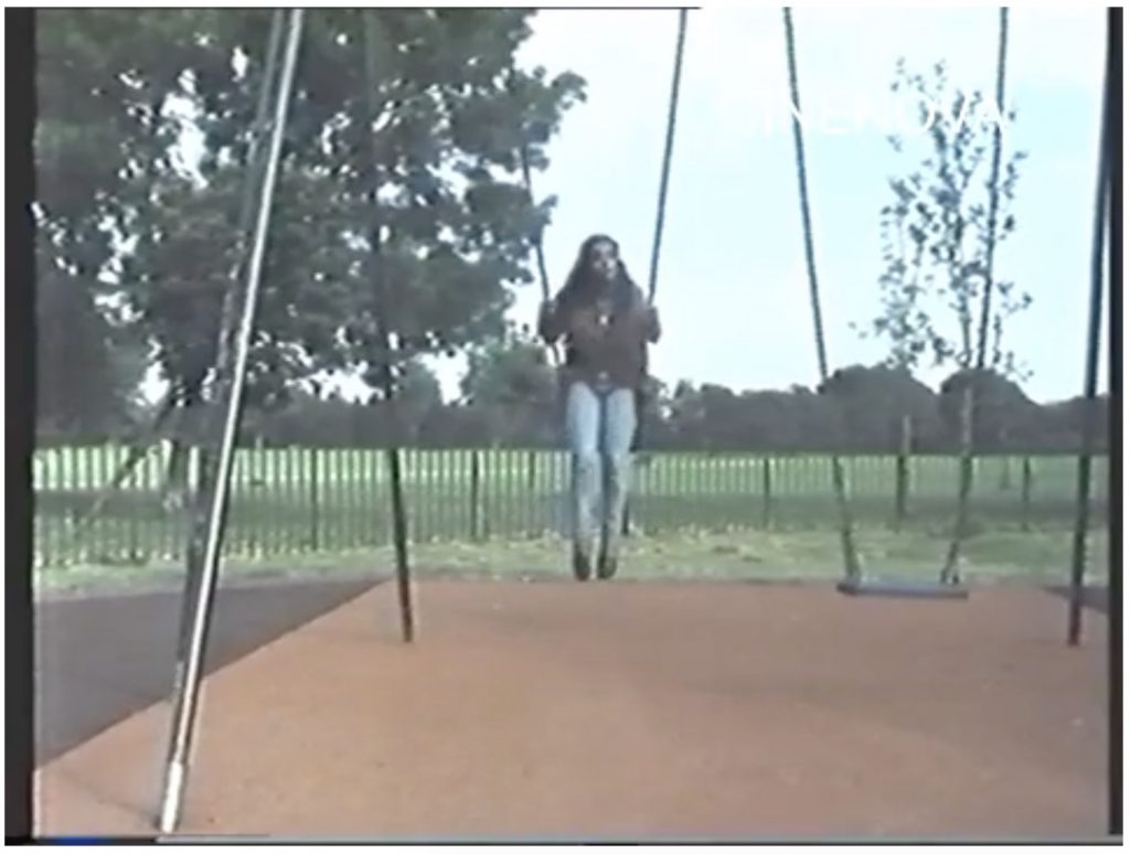 The image is a screengrab from a colour film, watermarked CINENOVA in the upper right-hand corner. It shows a dark skinned woman wearing a reddish-purple shirt or jacket and blue jeans, swinging backwards on a playground swing. There is a sandy-coloured area beneath her, and grass and trees stretching behind her.
