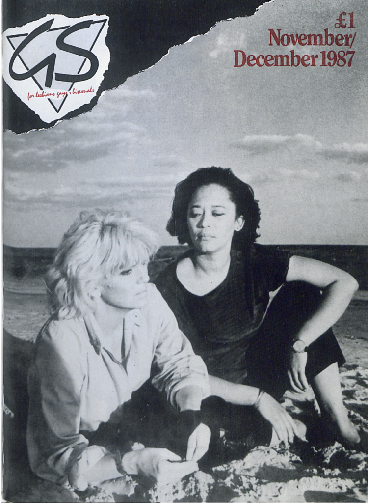 The image shows the cover of Gay Scotland magazine for November and December 1987. It features a black and white version of a still from She Must Be Seeing Things. The image show two women in the foreground sitting on the beach. The sea and sky are open and calm behind them, with a few light clouds in the sky. There is a light-skinned, light-haired woman closer to the camera, wearing a pale shirt and dark trousers. She is holding a shell in her right hand, and leaning on her left elbow in the sand. A dark-skinned, dark-haired woman sits more upright behind her and to the left, close to her and watching her. She is wearing a dark, velvety-looking short sleeved top and dark cropped trousers. She has her left leg propped up, and her left arm curled around her knee.