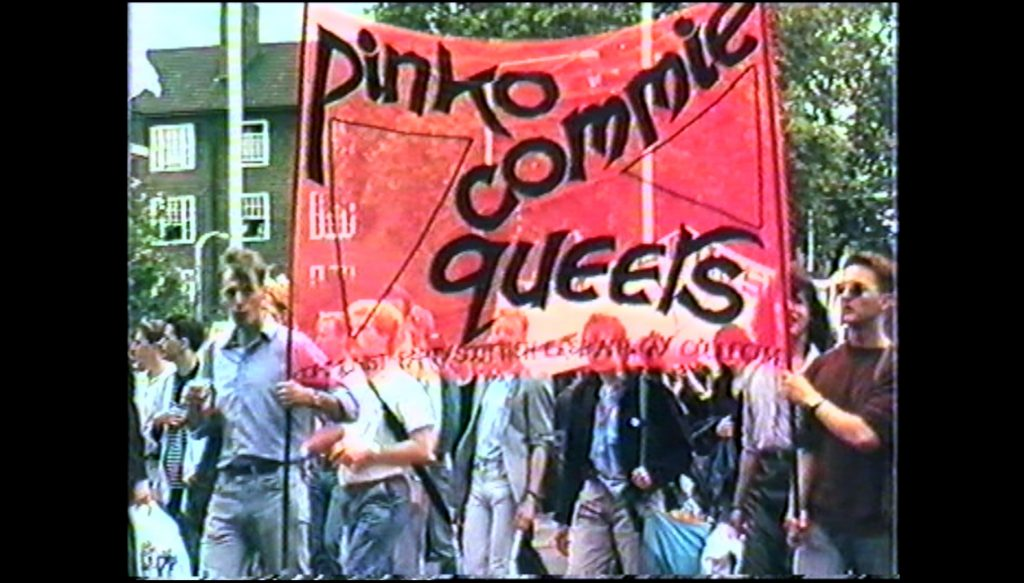 "The image is from the film Rebel Dykes. It is an archival image from footage of a protest march, showing a group of people in jeans and casual clothing holding a large pink banner that reads, all in lower case, ""pink commie queers,"" with the words arranged around two triangles."