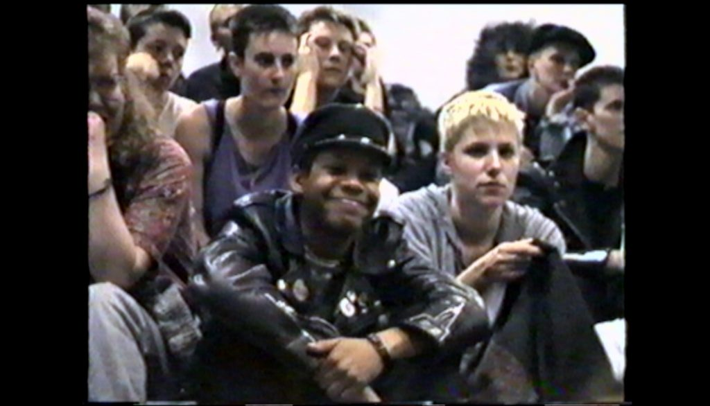 The image is a still from the film Rebel Dykes. It is taken from archival footage of a lesbian community meeting about BDSM. One of the film's main speakers, Debbie Smith, is in the centre of the image, surrounded by other audience members in punky clothing. Debbie, who is smiling, is a Black woman wearing black leather cap and jacket, with badges on the lapels.