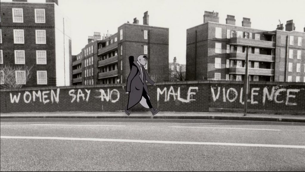 "The image is from the film Rebel Dykes, showing a frame of animation by Harri Shanahan over a background photograph taken by Jill Posener. The photography is of a flyover with a housing estate's blocks in the background. Pale coloured graffiti on the wall of the flyover reads WOMEN SAY NO TO MALE VIOLENCE. An animated figure with a shaved head and dark-coloured forelock, wearing a trench coat, is striding past the bridge and standing in front of the word ""TO."""