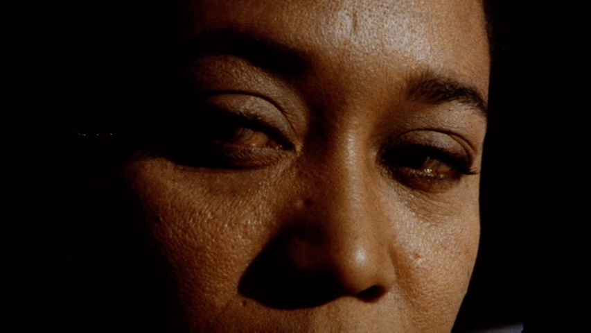 The image is a still from a colour film. It shows a dark-skinned woman's face in extreme close up against a black background. She is looking off to the left, and her eyes are bloodshot as if she has been crying. She is dramatically lit, with the left side of her face in shadow.