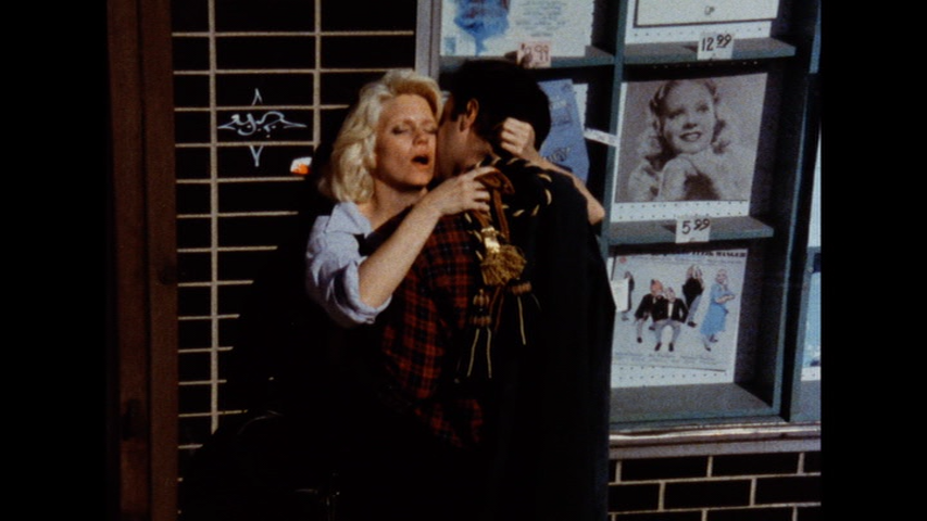 The image is a still from a colour film. It shows a blonde-haired, light-skinned woman wearing a pale blue sweater and facing toward the camera: she is backed up against the window of a closed record store, and she is being embraced by a light-skinned man in a long dark coat and red plaid scarf. The woman has her eyes closed and looks aroused by the embrace.