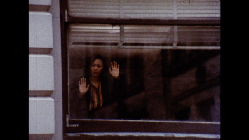 The image is a still from a colour film. It shows a woman looking out of a large window. The woman is wearing a dark jacket over a lighter-coloured top. She has dark hair, and she has her hands pressed against the glass. There is a shutter reflected in the window above her.