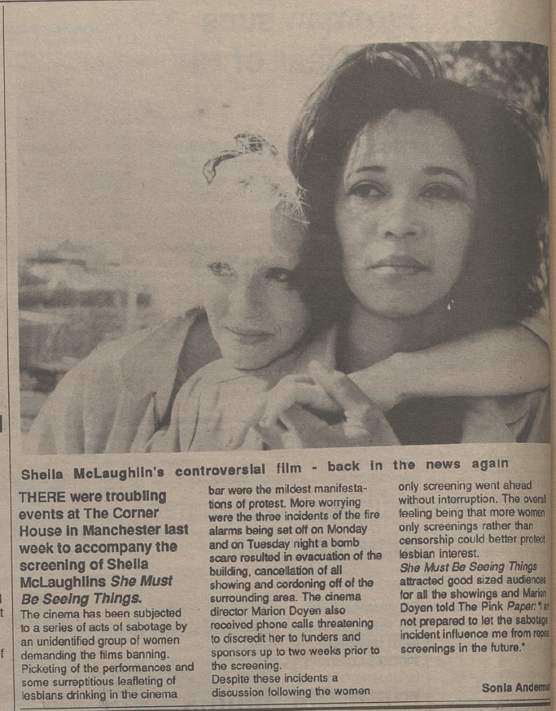 """The images shows a page from a newspaper. The top half of the image features a black and white still from She Must Be Seeing Things, showing a dark-skinned, dark-haired woman in the foreground, with a light-skinned, light-haired woman standing behind her, leaning against her with one arm around her shoulder. The headline reads """"Sheila McLaughlin's controversial film – back in the news again."""""""