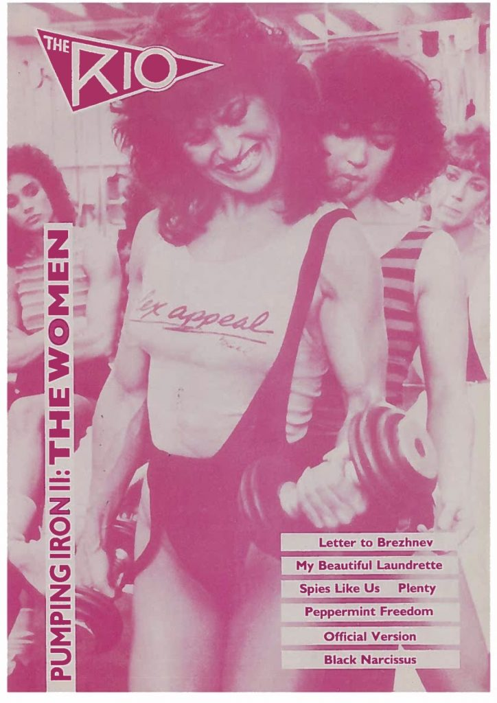 """The image is a hot pink tinted cover for a Rio Cinema programme from 1985, featuring a still from Pumping Iron II: The Women that shows a female bodybuilder lifting a weight in her left hand. She is wearing a low cut leotard over a vest that has the slogan """"Flex appeal."""""""