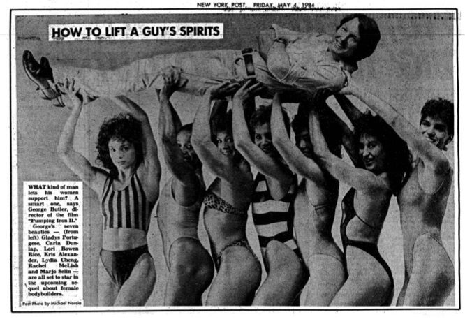 """The image is the New York Post, Friday May 4 1984. It is a photograph promoting Pumping Iron II. The headline is """"How to Lift a Guy's Spirits"""". The image shows seven toned, muscular women in bikinis, with different skin tones and hair styles. They are smiling and lifting a white man above their heads. The text box on the side reads """"What kind of man lets his women support him? A smart one, says George Butler, director of the film Pumping Iron II. George's seven beauties – (from left) Gladys Portuguese, Carla Dunlap, Lori Bowen Rice, Kris Alexander, Lydia Cheng, Rachel McLish and Marjo Selin – are all set to star in the upcoming sequel about female bodybuilders."""" Post photo by Michael Norcia."""