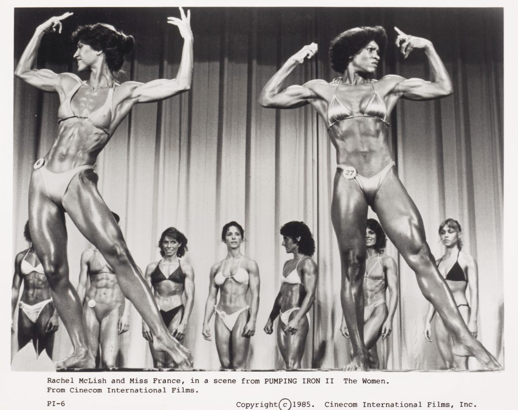 The image is a black and white publicity still from the film Pumping Iron 2: The Women. It shows two of the competing female bodybuilders, Rachel McLish and Miss France, at the front of the stage, with a line of other competitors behind them. The two women at the front are posing with their arms raised, flexing their biceps. All the women are wearing bikinis and are glossy with oil. They have a range of skin tones, hairstyles and facial expressions.