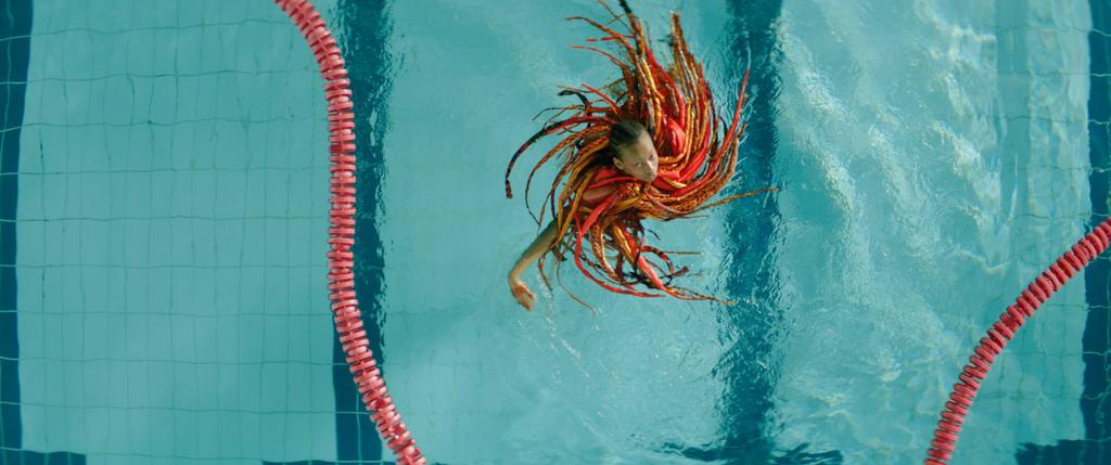 The image is a colour still from the short film Anemone. It is a crane shot above a swimming pool with clear turquoise water. There is a red lane rope barrier that snakes across the surface of the water curving around a figure in the middle of the image. The figure is Anemio, and they are brown-skinned with long dark hair that is intermingled with a collar of red, orange and gold ribbons and feathers.