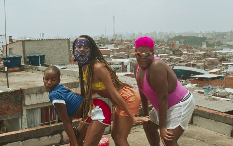 The image is a colour still from the short film Bonde. It shows three dark-skinned women dancing on a rooftop with a hazy city skyline stretching behind them. The woman on the left has a shaven head, and is wearing a blue T-shirt with the sleeves rolled up, and red and white shorts. She is leaning over with her hands on her knees and her butt raised, and pressed against the belly and crotch of the woman behind her, who has waist-length braids that hang over her friend's back. The second woman is wearing a matching navy bandanna and face mask, and a bright yellow crop top and orange short shorts. She is leaning over with her knees slightly bent and her hands turned out. The third woman is leaning in with her hands on her knees. She has close-cropped, neon-pink hair and she is wearing mirror shades, a pink vest and white shorts.
