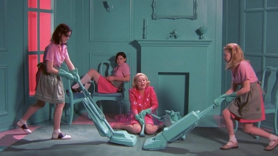 The image is a colour screenshot from the film But I'm a Cheerleader. It shows a life-size model of a pale blue living room, with a false fireplace and false window. Two characters in pink dresses and grey aprons are pushing pale blue vacuum cleaners from opposite sides of the room. An older woman in a pink cardigan and skirt sits on the floor instructing them. Another character in pink sits sideways on a chair in the background.