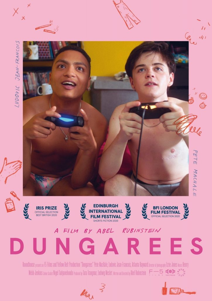 The image is the poster for the short film Dungarees. In the centre of the top two-thirds of the poster is a photograph of two young men, one with darker skin and one with lighter skin: they are both shirtless and in their underwear. Both are holding video game controllers and looking intently at a screen. The background of the poster is candy pink, with sketches of dungarees, nail varnish, cigarettes and kisses scattered around the central image, along with the performers names Ludovic Jean-Francois and Pete MacHale. Beneath the photograph there are three blue wreaths indicating the film was screened at the Iris Prize, Edinburgh International Film Festival and BFI London Film Festival. Beneath them the film's director and title are stated in hot pink capitals reading A FILM BY ABEL RUBENSTEIN, DUNGAREES.