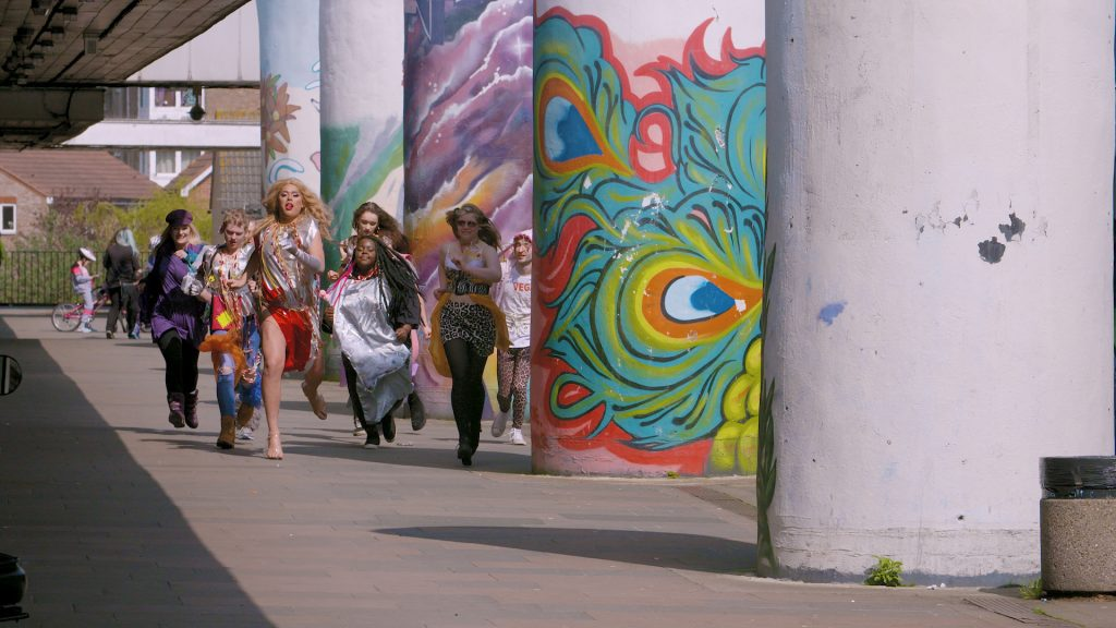 The image is a colour still from the short film Laindon. It shows a group of people running past large concrete columns covered with colourful graffiti: one column has a shape like a peacock feather, the column behind has a purple skyscape. The group of people are in the middle distance, and they are wearing colourful, summery clothing.