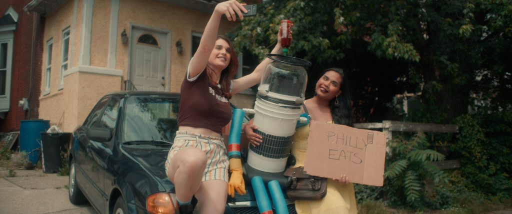 The image is a colour still from the short film Trashy Booty. It shows two women and one robot sitting on the front of a car outside a house. The house is yellow with a white door, and the front yard is full of large trees in leaf. The car is dark blue. One woman is pale-skinned, wearing a brown T-shirt and striped high-waisted short. She is holding her cell phone up above head-height to take a selfie showing her squeezing chilli sauce onto the vinyl plate on top of the robot's head. The other woman is hugging the robot with her right arm, and holding a cardboard sign that says Philly Eats with her right. She is darker-skinned with long dark wavy hair, and she is sticking her tongue out and crossing her eyes for the camera. She wears a yellow sundress and carries a leather satchel. The robot has a glass domed head, a white cylindrical body, and bright blue foam arms and legs. Its hands are yellow rubber gloves.