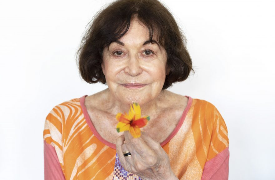 The image is a colour photograph showing the artist Claudia Andujar. She is an older woman with white skin and dark hair cut in a bob. She is wearing a wide-necked top with orange abstract markings like ferns or feathers, and with pink sleeves. She has a slight smile, and is holding a vibrant yellow and red flower up to the camera.