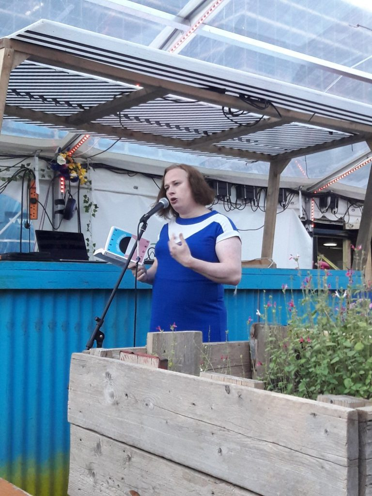 The image is a colour photograph showing Juliet Jacques reading from Variations at Grow Tottenham. Juliet is a white woman with shoulder-length brown hair. She is wearing a short-sleeved blue dress with a white shoulder yoke. She is standing behind a microphone holding a copy of her book. In the foreground there is a wooden planter with wild flowers blooming, in the background there is a corrugated fence painted blue. The roof is made of transparent plastic.