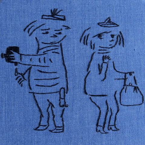 The image is a piece of embroidery in black thread on a blue background. It shows a drawing from Travels with Tove, depicting Tuulikki Pietilä in the clothing of the Moomin character Too-ticky – a tam, a striped sailor's top, and trousers – holding an 8 mm film camera. She is looking over her shoulder at Tove, who also wears a tam, a sweater and high-heeled boots, and is carrying a large handbag reminiscent of Moominmamma's.