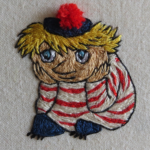 The image is a piece colour embroidery depicting the Moomin character Too-ticky. Too-ticky has white skin and blond hair, and wears a blue tam with a red bobble, a red and white striped shirt, and blue trousers. The embroidery shows Too-ticky sitting head in hands as if concentrating on something.