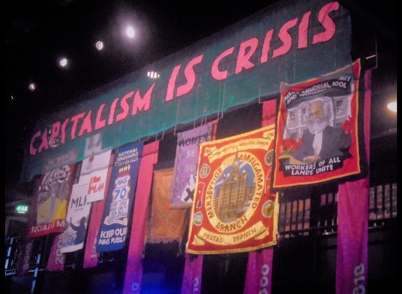 """The image is a colour screenshot from Juliet Jacques' digital presentation Aphorisms on Self-Care (2020). It shows a display of banners, with a large horizontal banner at the top that reads """"capitalism is crisis"""" in pink capitals on a green background."""